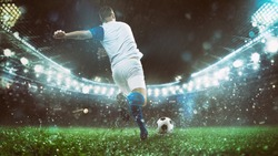 Close up of a soccer scene at night match with player in a white and blue uniform kicking the ball with power