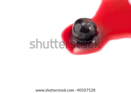 Close-up of a solitary blackcurrant in redcurrant juice, isolated on white background.  Seated on right side of frame with copy space to the left.