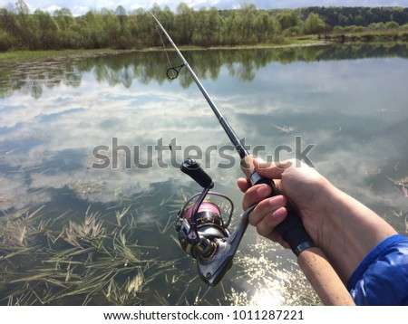 close-up of a spinning in the fisherman's hand against the background of the lake and forest. #1011287221