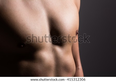 Close up of a sports man's chest. Muscular man on a dark background #415312306