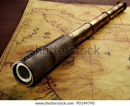 Close-up of a spyglass on the old map #90144790