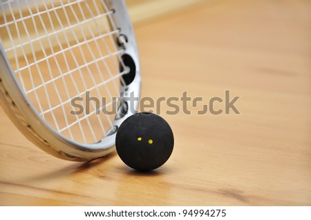 Close up of a squash racket and ball over wooden background