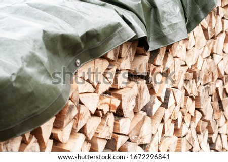 close-up of a stack of chopped firewood covered with a tarpaulin Сток-фото ©