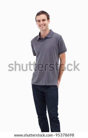 Close-up of a standing man smiling with his hands behind his back against white background - stock photo