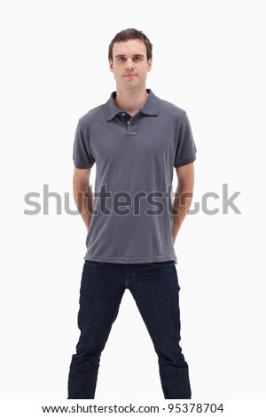 Close-up of a standing man with his hands behind his back and his legs apart against white background