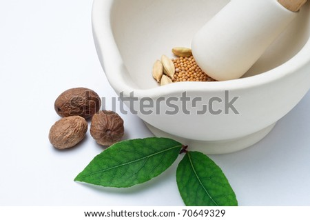 Close up of a stoneware pestle and mortar containing a mixture of whole spices, with nutmegs and bay leaves on the surface outside it. Horizontal (landscape) orientation.