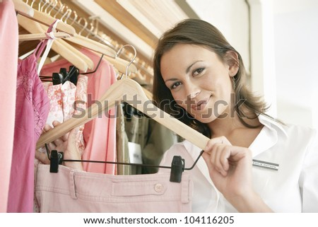 Close up of a store assistant sorting clothes on store\'s rails, smiling.