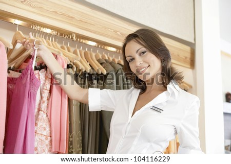 Close up of a store assistant sorting clothes on store's rails, smiling.