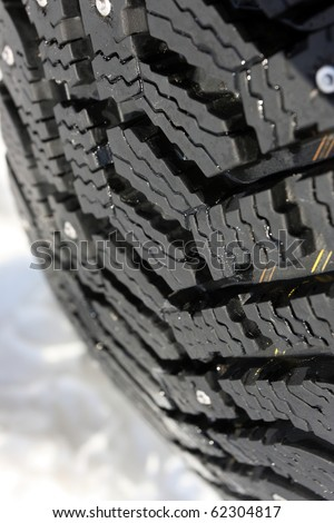 Close-up of a studded tire tread on the snow