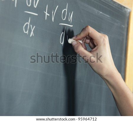 Close-up of a student's hand solving maths problem