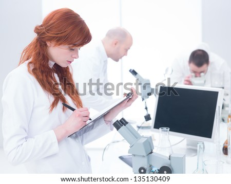 close-up of a student taking notes in a chemistry lab with another two scientists analyzing under microscope in the background around a lab table