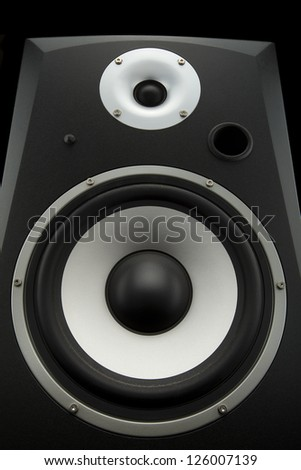 close up of a studio monitor speaker isolated on black background shot from a low angle