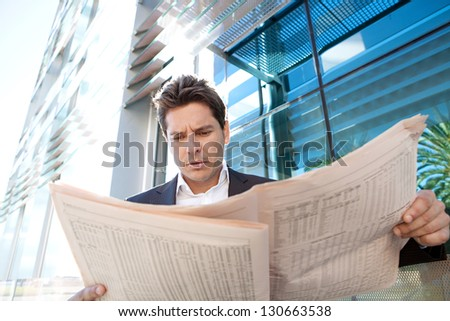 Close up of a successful businessman standing by a modern office building reading the stock shares pages of a financial newspaper, outdoors.