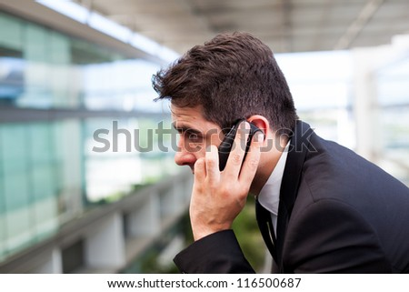 Close-up of a successful young business man talking on cell phone at modern office