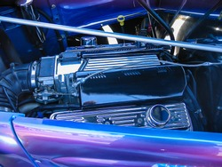 Close-up of a supercharger on a vintage hotrod, with blue colors reflected on chrome engine components.