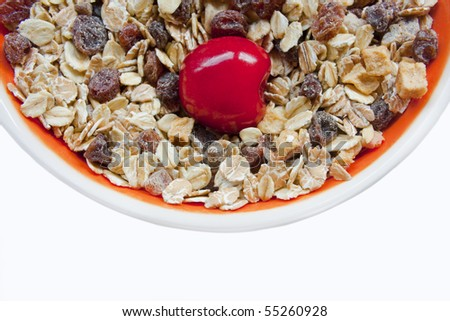 Close up of a sweet cherry in a bowl of muesli and raisins.