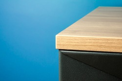 Close-up of a table corner solid wood furniture detail with blue background
