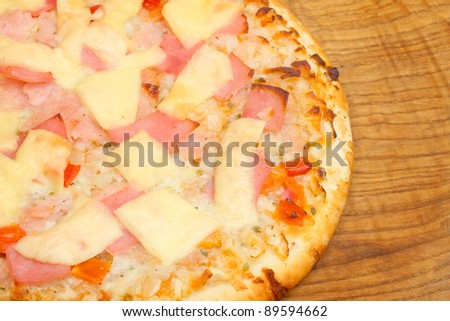 Close up of a tasty pizza with ham and cheese.
