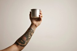 Close up of a tattooed man's hand with a steel travel cup against white background Alternative coffee brewing commercial