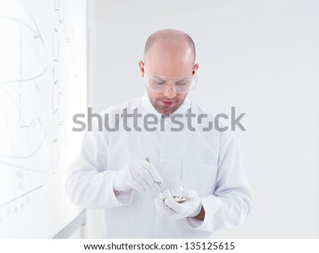 close-up of a teacher in a chemistry lab holding in hands a forceps with a pill in it