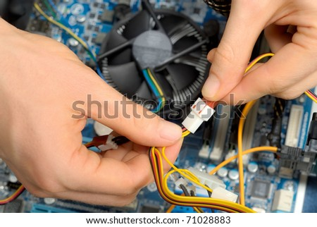 Close up of a technician's hands wiring computer parts
