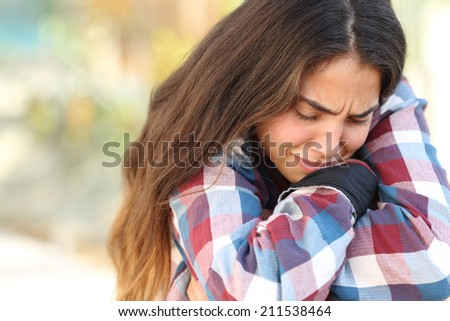 Close up of a teenager girl worried and sad crying outdoors