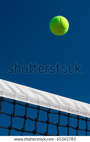 Close-up of a tennis ball going over the net with a blue sky background. - stock photo