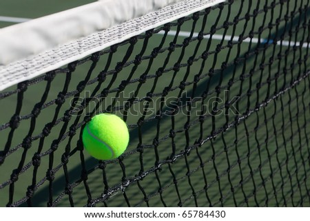 Close-up of a tennis ball hit into the net.