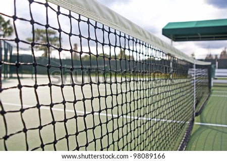 Close up of a tennis net and court on a sunny and cloudy day.