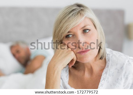 Close-up of a tensed mature woman sitting in bed with man in background at home