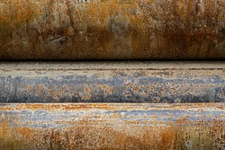 close up of a texture of steel pipes, gray, steel gray and rust colored