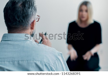 Close-up of a therapist holding a pen talking to his blurred female patient #1143268391
