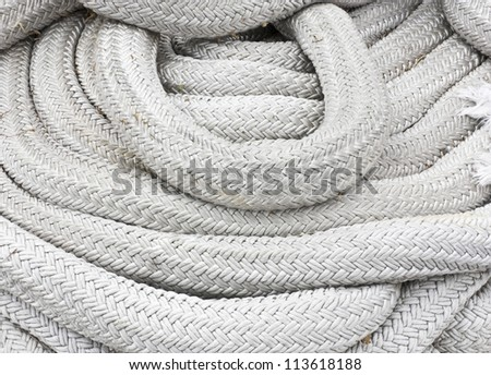 Close up of a thick, heavy, woven white rope used for securing boats to a dock.