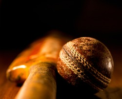 Close up of a thrashed and worn out cricket ball (season ball) next to a cricket bat on wood.