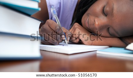 Close-up of a tired afro-american teen girl studying in a library