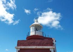 Close up of a Top of lighthouse tower with a round white metal roof and arrow under blue caribbean sky. Lighthouse tower containing the lamp, lens, watch room and gallery deck. Architecture detail.