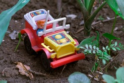 Close up of a toy jeep for kids placed on a muddy surface, small plants around it, selective focus