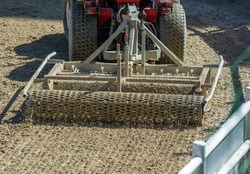 Close up of a tractor preparing the Field before an Equestrian competition in Italy on Blurred Background