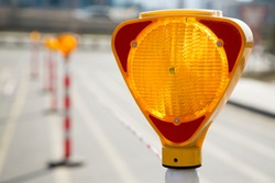 Close-up of a triangle-shaped flasher traffic warning light, which is positioned to ensure traffic safety.
