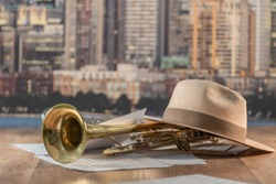 Close-up of a trumpet, a hat and musical sheets