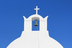 Close up of a typical Greek whitewashed bell tower with a cross on top. Blue sky in the background. Santorini, Greece