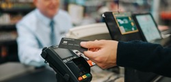 Close-up of a unrecognisable person using credit card to pay at grocery store. Customer making a payment for the purchase using his nfc card at supermarket.