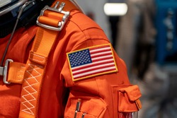 Close up of a USA flag on a space suit.