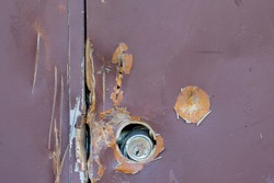 Close-up of a vandalized metal door showing severe dents and scratches.