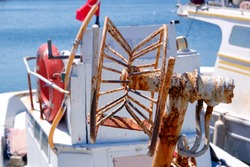 Close-up of a very old, rusty trawl / bow winch on the deck of small fishing boat in summer. Background for fishing. Focus on foreground.