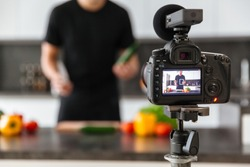 Close up of a video camera filming young male blogger at the kitchen