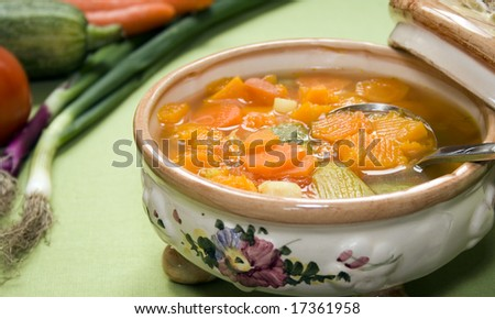 Close up of a vintage ceramic saucepan full of vegetable soup. Focus on the soup.