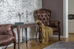 Close up of a vintage table and an armchair in a classical interior in italian style. Dark wooden furniture on a light walls, wooden floor. A perfect place to take rest.