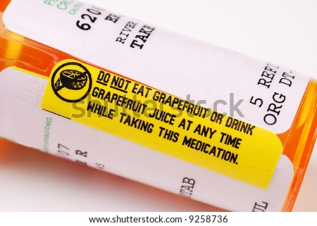 Close-up of a warning label about consuming grapefruit on a bottle of prescription medication.