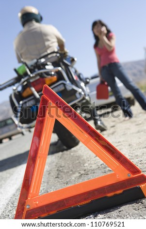 Close-up of a warning triangle with woman and traffic cop